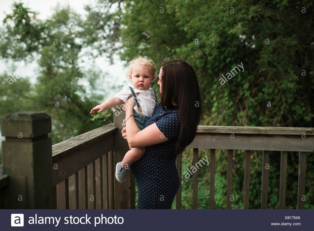 Mulher grávida carregando toddler filho na varanda Imagens de Stock