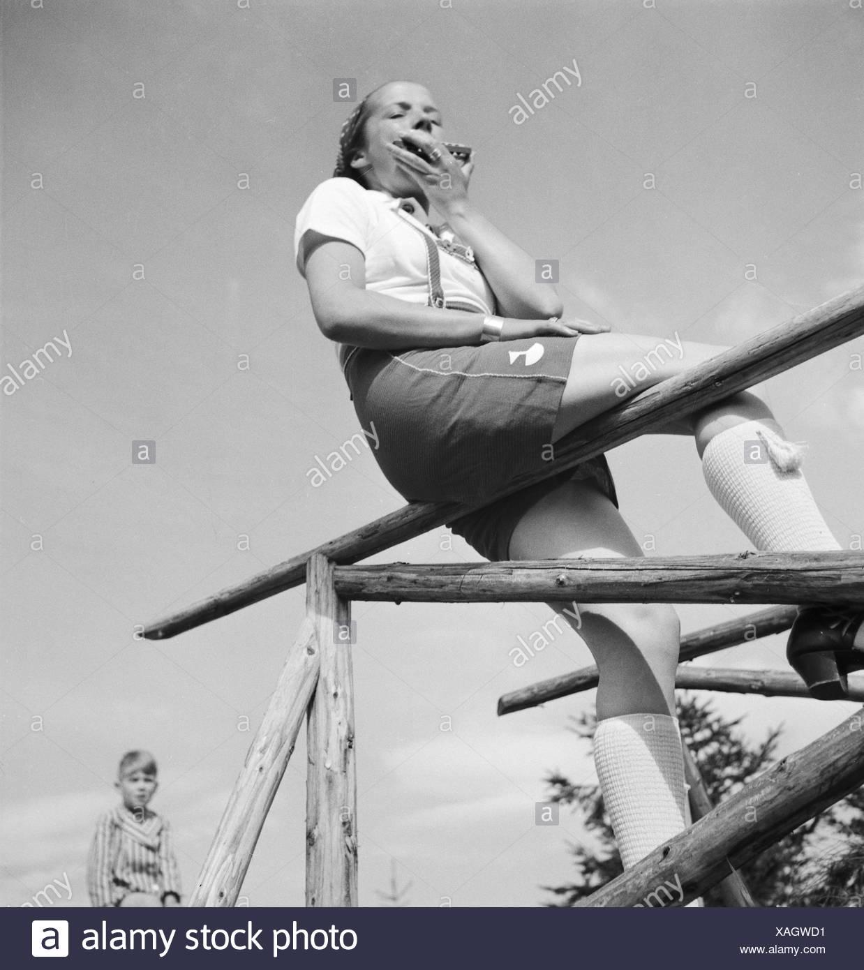 Eine junge Frau mit einer Mundharmonika auf einem Zaun, Deutschland er Jahre 1930. Uma mulher jovem com uma harmonica sobre uma cerca, Alemanha 1930. Imagens de Stock