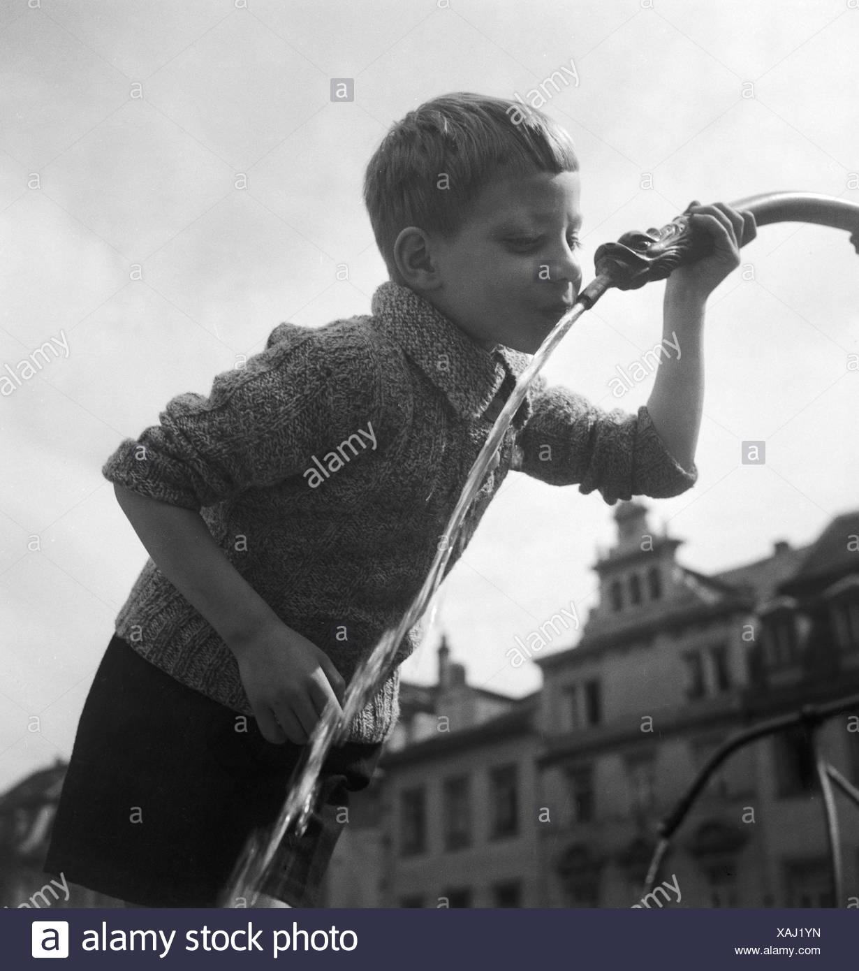 Ein Junge trinkt Wasser aus einem Brunnen, Deutschland er Jahre 1930. Um rapaz de água potável a partir de uma fonte, Alemanha 1930. Imagens de Stock