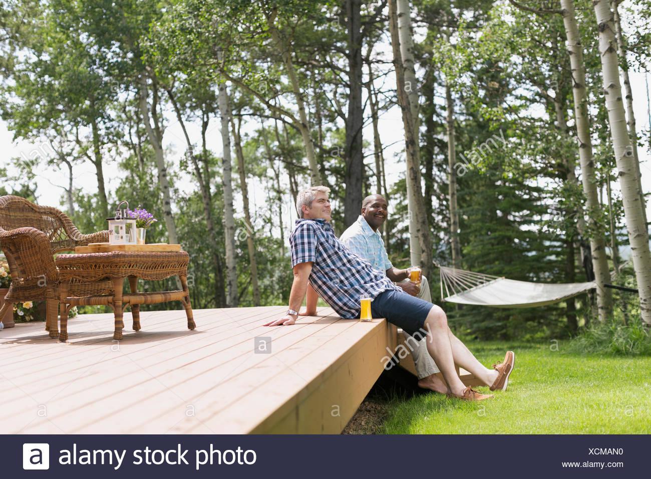 Homens desfrutando de bebidas em um deck ao ar livre Imagens de Stock