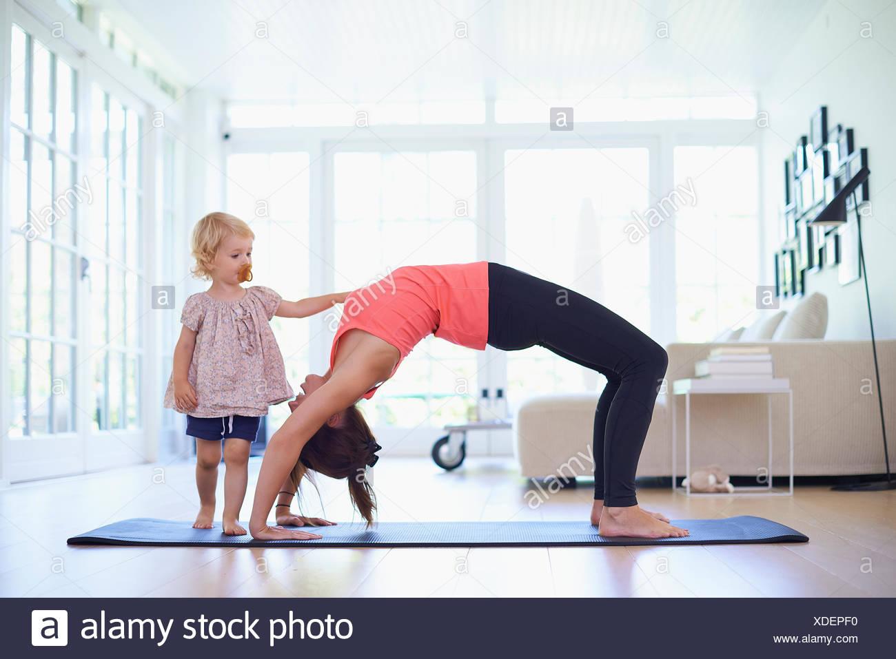 Meados de adulto mãe praticam ioga com curioso toddler filha Imagens de Stock