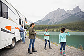 family-standing-at-lakeside-near-rv-E5NA