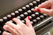 hands-on-typewriter-close-up-AT6E7R.jpg