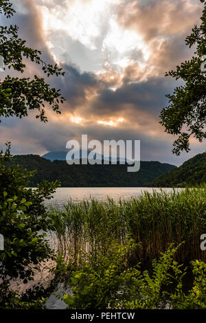 Sunset over the lake and reeds at Levico Terme, Trentino, Italy - Stock Image
