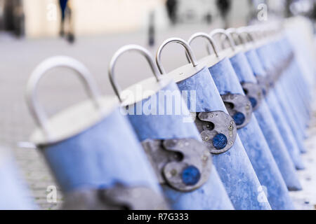 color isolation, shared bike rental station empty due to winter season in Warsaw Poland, lock close up, blurred background - Stock Image