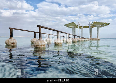 DEAD SEA, ISRAEL. 6TH FEB 2016: Submerged pier in crystalline water with salt formation where its rails meet the water. - Stock Image