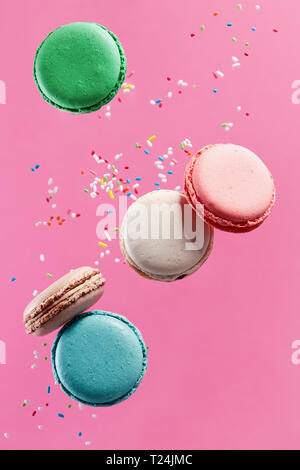 Traditional french colorful macarons on pink background. - Stock Image