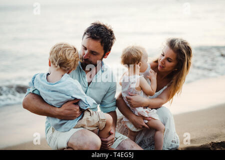 A family with two toddler children sitting on sand beach on summer holiday, playing. - Stock Image