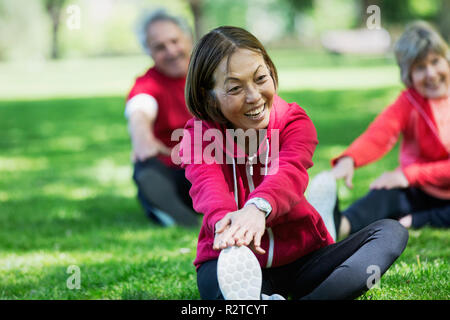 Happy active senior woman stretching leg in park - Stock Image