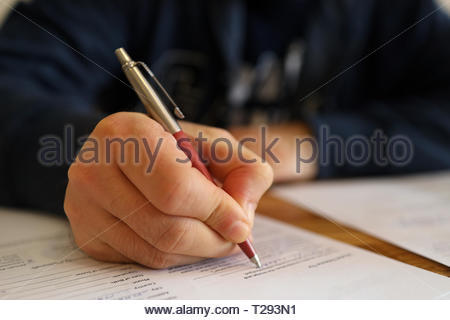 Man hand with pen. Close up of the hand of a man fill in a contract. Selective focus on hand. Blurred content - Stock Image