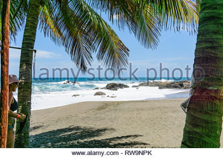 A woman showers after swimming in the Pacific coast surf at the beach at Las Peñitas, Nicaragua. - Stock Image