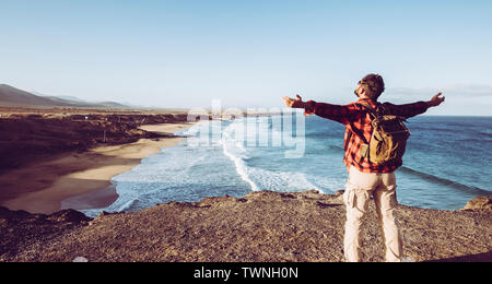 Standing man feel the nature outdoor opening arms in front of a wild beautiful beach from the top of a cliff - alternative backpack vacation for hipst - Stock Image