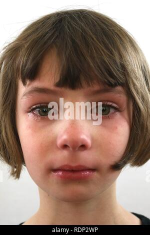 Portrait of an upset defiant little girl with tears of frustration in her eyes - Stock Image