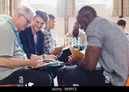 Men reading paperwork in group therapy in community center - Stock Image