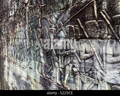 Angkor Wat details on wall of carved drawings of tribes of people - Stock Image