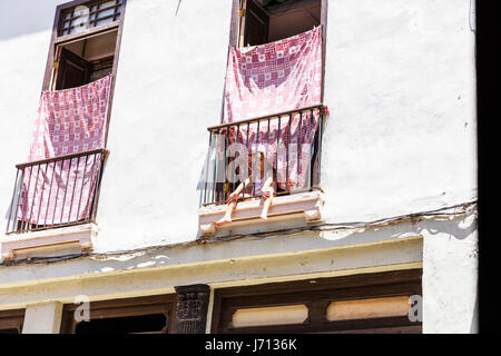 Young boy on hotel balcony alone, young boy looking through railing on hotel balcony, child on balcony, Havana Cuba - Stock Image