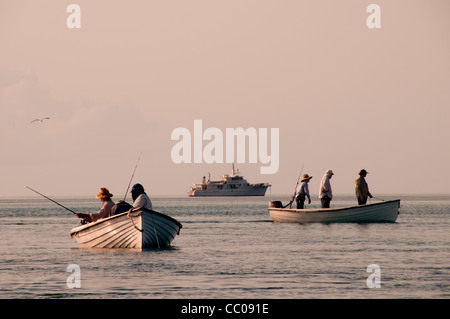 Small boats fishing in the late afternoon, with the mothership in the background, on a very calm day on Swains Reef - Stock Image