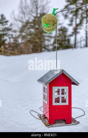 Red outdoor birdhouse or feeding station for birds in winter against snow covered landscape - Stock Image