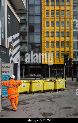 Yellow architecture and construction waste bins at St. Giles at the end of Denmark Street, on 4th March 2019, in London England. - Stock Image