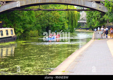 People walking along the Regent's canal with group of canoe's  passing under the bridge on a warm summers day - Stock Image