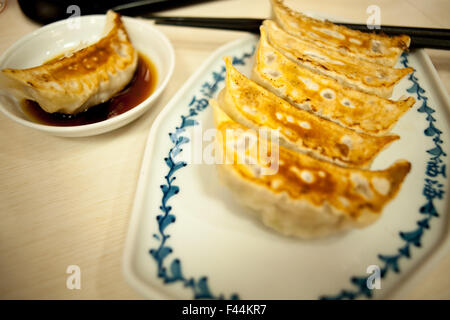 Gyoza pot stickers on a plate one in sauce tray - Stock Image