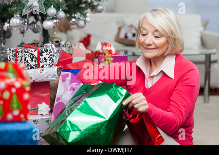 Woman Looking In Bag While Sitting By Christmas Presents - Stock Image