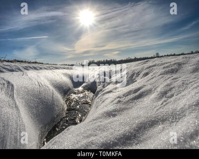 Hole in icy snow with sun flares. Lovely winter scene. - Stock Image