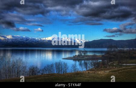 Snow covered mountain range back a Fjord in Western Norway. - Stock Image