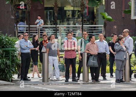 People wait to cross at an intersection on Orchard Road in central Singapore city - Stock Image