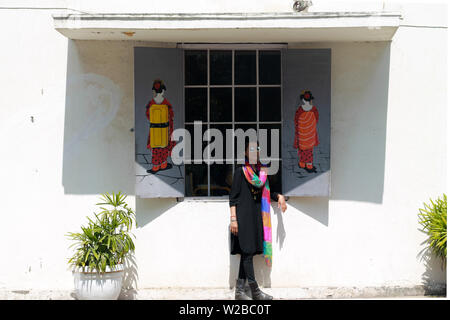 A young beautiful Indian woman model in black dress having fun and posing in front of the window of a Chinese cafe with graffiti artwork on the wall. - Stock Image
