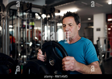 A senior man doing strength workout exercise in gym. Copy space. - Stock Image