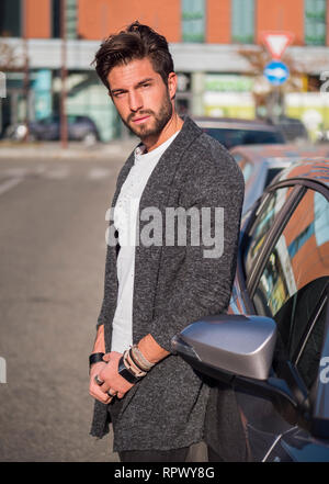 Handsome young man next to car in white shirt - Stock Image