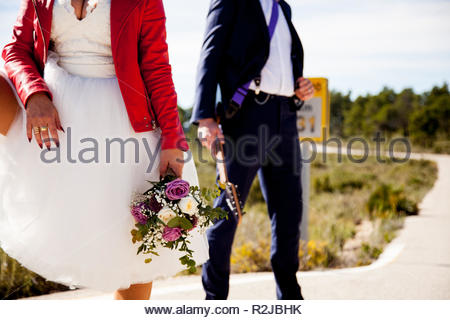 A woman dressed as a bride, with a red jacket and a bouquet, waits next to a man dressed in a suit and an electric guitar on a lonely road. - Stock Image