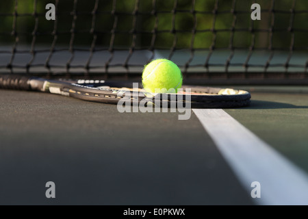 Tennis racket and ball on court by net. - Stock Image