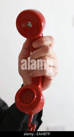 Man's hand holding an old red telephone. - Stock Image