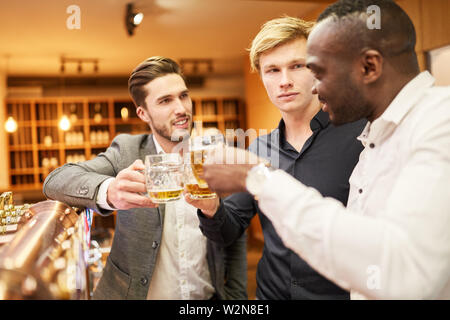 Men brag to beer at the counter during a pub crawl as a men's night - Stock Image