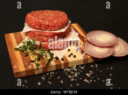 Beef burgers handmade prime beef, on a wooden board on a Black background. - Stock Image