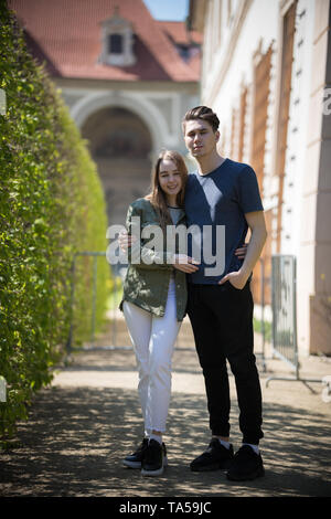 A young couple traveling. Standing on the street and hug. Mid shot - Stock Image
