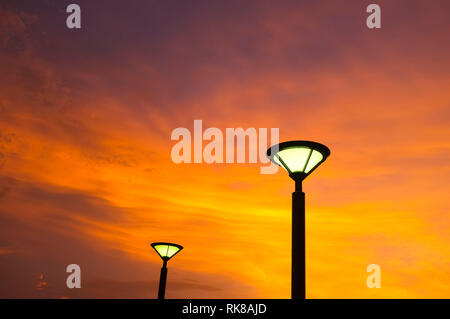 Street lights against an orange sky at sunset. - Stock Image