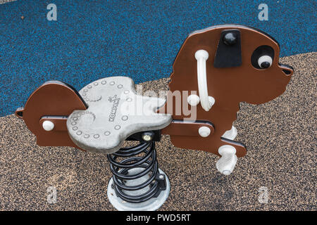 HICKORY, NC, USA-10/14/18: A spring-mounted rocking dog, usually made as a rocking horse, in an outdoor playground. - Stock Image