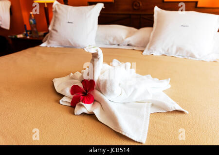 Bed Suite decorated with flowers and swan towel, bed decoration  bed, bedding, bedroom, decorated, decorating, decoration, - Stock Image