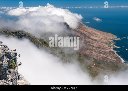 Abseilers abseiling off the summit of Table Mountain with Cape Town's Atlantic coastline in the background. - Stock Image