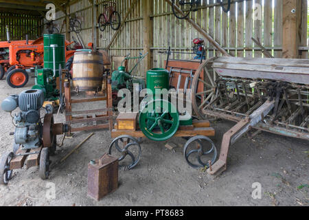 Display of historic farm machinery including portable engines and a butter churn Ryedale Folk Museum in Hutton le Hole North Yorkshire England UK - Stock Image