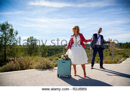A woman dressed as a bride, with a red jacket, a bouquet and a suitcase waiting next to a man dressed in a suit and an electric guitar on a lonely roa - Stock Image