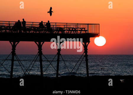 Aberystwyth, UK. 10th Apr, 2019. UK Weather: At the end of a day unbroken blue skies and warm spring sunshine, the sun sets  spectacularly behind the silhouettes of people enjoying a drink on the seaside pier in Aberystwyth on the Cardigan Bay coast of West Wales. Credit: keith morris/Alamy Live News - Stock Image