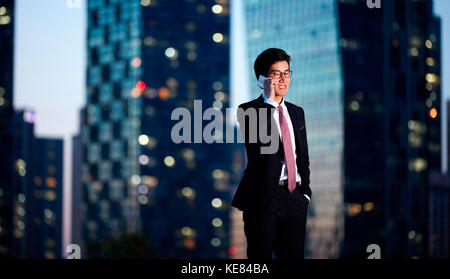 Smiling businessman talking on cellphone in city at night - Stock Image