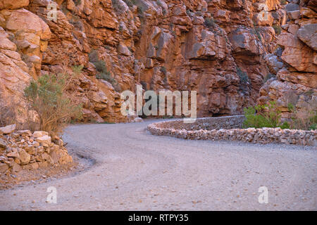 S curve gravel road carved into orange colored rocky canyon - Stock Image
