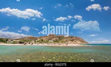 Agia Galini Beach in Crete island, Greece. Tourists relax and bath in crystal clear water of Agia Galini Beach. - Stock Image