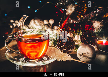 Christmas postcard with hot cup of tea and decorations. Winter holidays concept - Stock Image