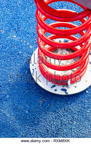 Close up of a red spring swing equipment on a blue pavement. - Stock Image